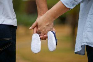 Padres dandose la mano y sujetando las zapatillas del bebe